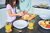 Mother and daughter cutting bananas in kitchen