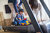Happy mother and kids with toys on treadmill