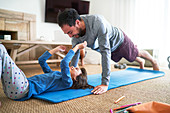 Playful father and daughter exercising
