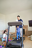 Mother and son walking on treadmill in living room