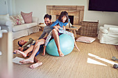 Playful father and kids on fitness ball