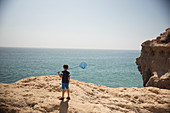 Boy with fishing net on rocks at ocean