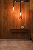 Modern pendant lights hanging over wooden shelf
