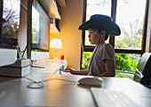 Boy in cowboy hat playing videogame