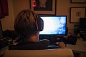 Teenage boy playing videogame in dark bedroom