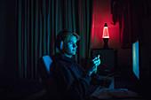 Boy in headset playing videogame in dark bedroom