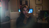 Boy with headset using smart phone in dark bedroom