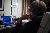 Teenage boy using computer in dark bedroom