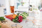 Vegetables and preserving jars on kitchen counter