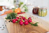 Close up red radishes and herbs on cutting board