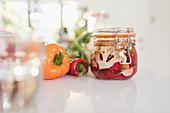 Preserved vegetables in jars on kitchen counter