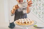 Woman sprinkling apple pie with powdered sugar