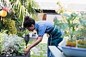Woman watering plants with spray bottle in garden