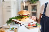 Woman holding cheeseburger on cutting board