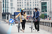 Business people in face masks walking bicycles