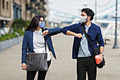 Business people in face masks touching elbows