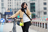 Woman with bicycle talking on smart phone in city