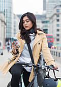 Woman on bicycle using smart phone in city