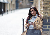 Woman using smart phone on city street