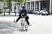 Playful man riding bicycle on city street