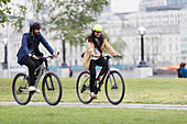 Business people riding bicycles in city park
