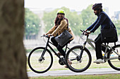 Happy couple in helmets riding bicycles in park