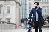 Businessman with bicycle talking on smart phone