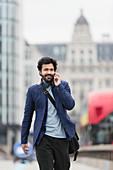 Businessman talking on smart phone in city