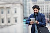 Businessman using digital tablet on city bridge