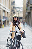 Portrait businesswoman with bicycle on city street