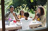 Happy family enjoying garden lunch on summer patio
