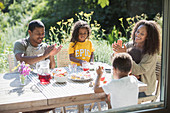 Family clapping and eating at summer patio table