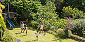 Family playing soccer in sunny summer backyard