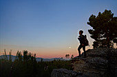 Young female hiker on rock in desert at dusk