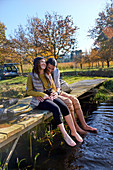 Affectionate barefoot couple laughing on dock