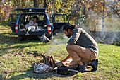 Man preparing campfire outside car in autumn field