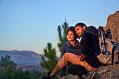 Serene hiking couple enjoying sunset on rocks