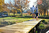 Barefoot couple walking on autumn lakeside dock