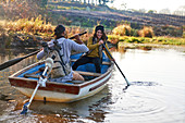 Happy couple with oars in rowboat on autumn lake