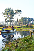 Young couple in rowboat on sunny tranquil pond
