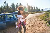 Couple piggybacking outside car at remote roadside