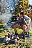 Happy couple enjoying campfire in autumn field