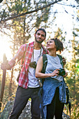 Couple hiking with camera and binoculars in woods