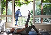 Senior woman stretching on yoga mat