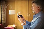 Senior man tasting red wine in living room