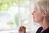 Senior woman smelling and tasting white wine