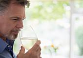 Senior man smelling and tasting white wine