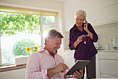 Senior couple using tablet and smart phone