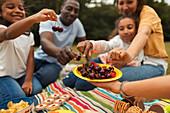 Family eating fresh cherries in park