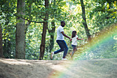 Father and daughter running on trail